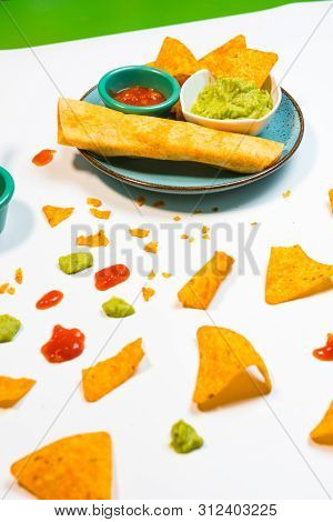 Guacamole Sauce And Spicy Sauce Accompanied By Nachos.
