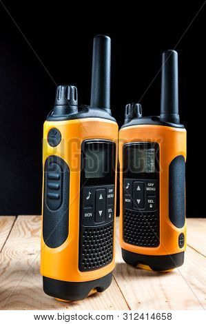 Two Walkie Talkie On Wooden Table On Dark Background