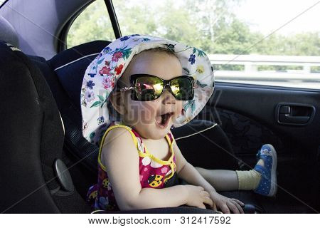 The Child Is Sitting In A Child Car Seat. A Child In A Hat And Sunglasses. Child Safety On The Road