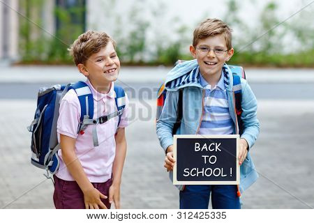 Two Little Kid Boys With Backpack Or Satchel. Schoolkids On The Way To School. Healthy Children, Bro