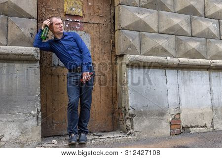 A Drunk Man Stands In The Alley With A Bottle Of Alcoholic Drink And Nervously Looks At Passersby