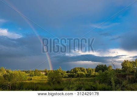 Multicolor Rainbow Against The Dark Cloudy Sky, Russia.