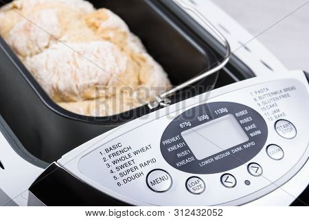 Homemade White Flour Bread Baked In Bread Maker With Digital Display.