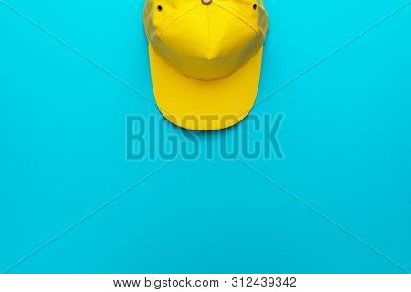Top View Of The Yellow Baseball Cap. Baseball Cap Over The Blue Torquoise Background. Minimalist Fla