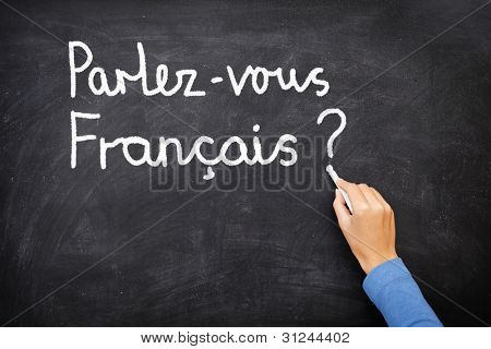 Learning language - French. Learning French language concept of teacher or student writing parlez-vous francais (do you speak French) on blackboard / chalkboard.