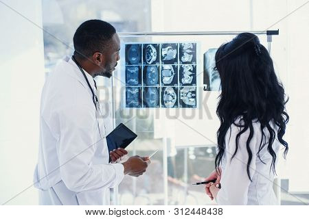 Two Doctors Look At An X-ray And Discuss The Problem. Medical Technicians Pointing At Mri X-ray Of P