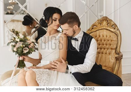 Tender Bride Posing With Handsome Fiance In Restaurant