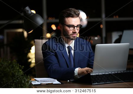 Young Man Working In Office At Night