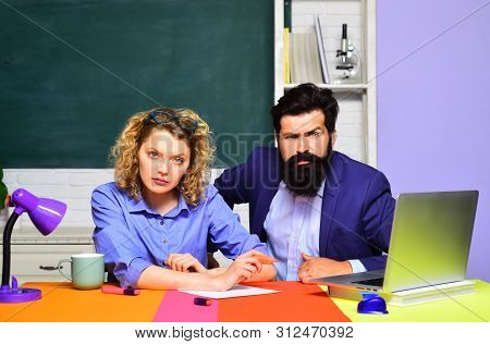 Happy Female Teacher With Male Student Over Green Chalkboard Background. Students And Tutoring Educa