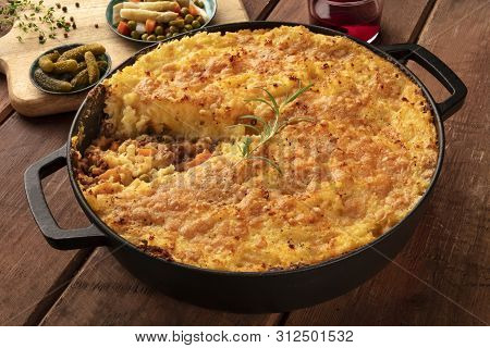 Shepherds Pie With Pickles, Herbs, And Red Wine On A Dark Rustic Wooden Background
