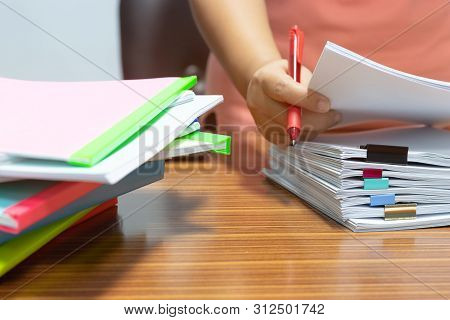 Teacher Hand Holding Red Pen For Checking Students Homework Assignment And Pile Of Unfinished Paperw
