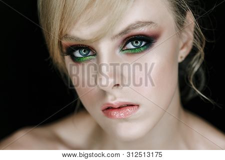 Serious Face Model with Face Make-up Closeup Photo. Stylish Glamour Girl with Angry Gaze and Professional Art Make-up Blonde Hairdo Head-dress Posing on Black Background Studio Portrait poster