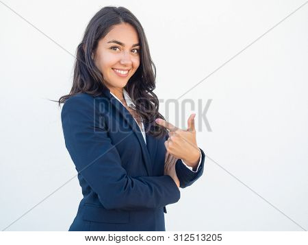 Cheerful female professional proud of herself. Happy beautiful black haired young woman in formal suit pointing index finger at herself. Self confidence concept poster