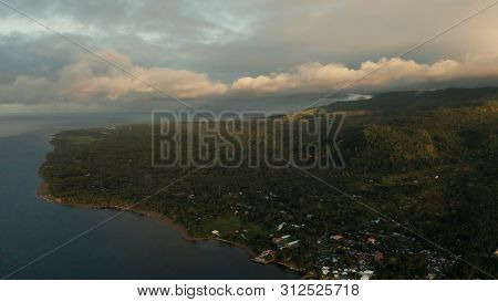 Coastline Of Tropical Island Covered With Green Forest Against The Blue Sky With Clouds And Blue Sea