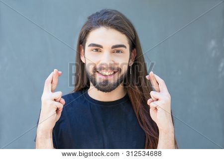Smiling young bearded man with piercing holding cross fingers. Stylish brunet with long hair and piercing in nose gesturing. Concept of good luck or nullify promise t of good luck or nullify promise poster