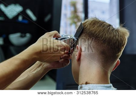 Male Haircut With Electric Razor. Barber Makes Haircut For Client At The Barber Shop By Using Haircl