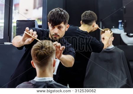 Barber makes hair styling with hair gel and comb after haircut at the barber shop. Young handsome Caucasian man getting a haircut in a modern hairsalon poster