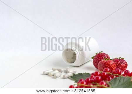 Vitamins Supplements As A Capsule With Fresh Berries From Medicine White Pill Bottle On White Backgr