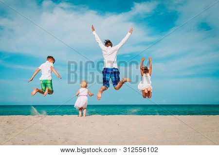 Happy Father With Kids-boy And Girls- Play At Beach
