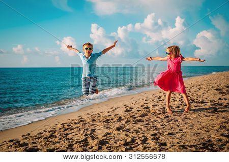 Happy Cute Boy And Girl Enjoy Play Jump On Beach