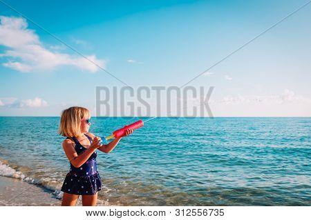 Happy Cute Girl With Water Gun On Beach