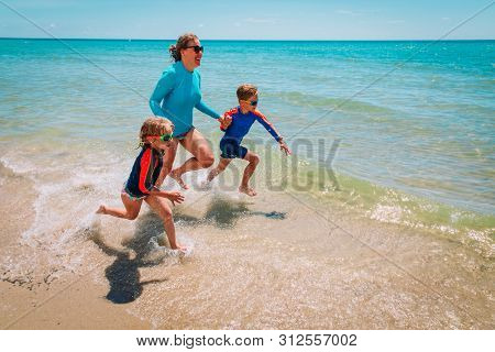 Mother With Kids Play With Water On Beach