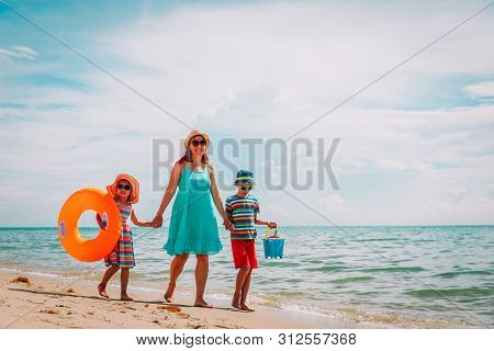 Mother With Son And Daughter Go To The Beach