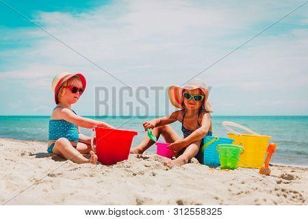 Cute Little Girls Play With Sand On Summer Beach