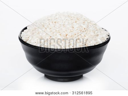 Black Bowl Of Raw Organic Arborio Risotto Rice On White Background.