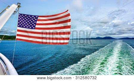 American Flag Flying Over The Blue Waters.
