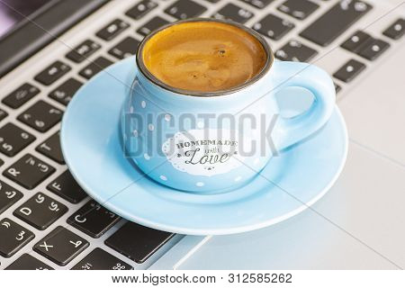 Turkish Coffee Inside Blue Cup On Keyboard Laptop At Morning