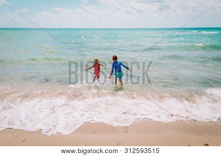Happy Boy And Girl Run Swim On Beach
