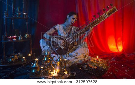 Beautiful Young Indian Woman In Traditional Sari Clothing With Oriental Jewelry Playing The Sitar. I