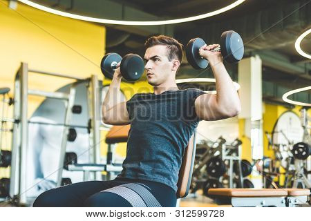 Working Out With Dumbbell Weights At The Gym.fitness Men Exercising Are Lifting Dumbbells. Fitness M
