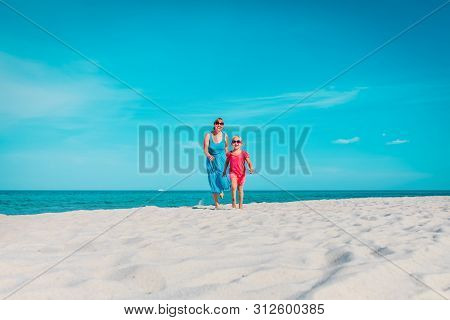 Happy Mother With Little Daughter Play On Beach, Family Run And Have Fun
