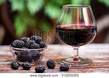 Close Up Fresh Mulberries Fruit In Bowl And Wine In Glass