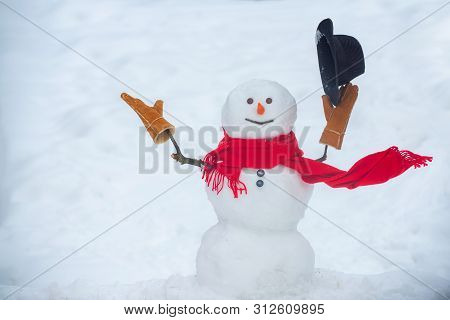 Hello Winter. Happy Snowman Standing In Winter Christmas Landscape. Happy Smiling Snow Man On Sunny