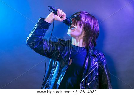 The Young Guy Is Singing In Microphone Rock Music On The Stage, Rock Concert Concept.