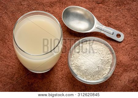 food grade diatomaceous earth supplement - powder and in a glass of water  with measuring scoop
