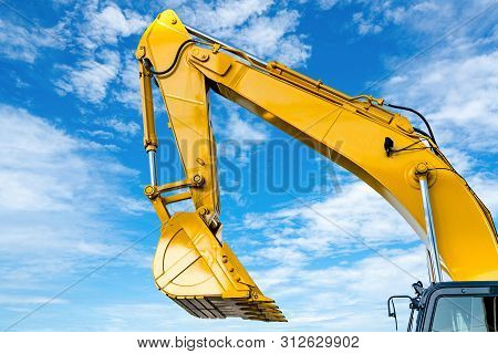 Yellow Backhoe With Hydraulic Piston Arm Against Blue Sky. Heavy Machine For Excavation In Construct