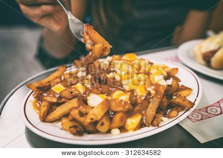 Poutine french fries canadian local classic dish in the province of Quebec, Canada. Fast food retro diner restaurant serving plate of fried potates with brown gravy sauce and fresh cheese curds.