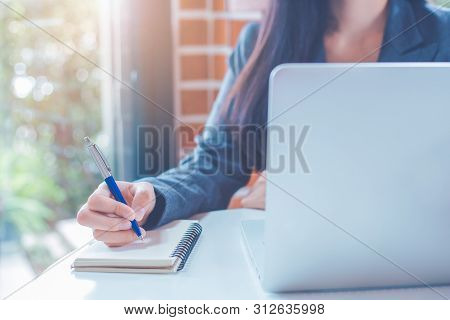 Business Woman Hand Is Writing On A Notepad With A Pen And Have A Laptop Computer On The Desk In The