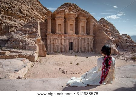 Asian Woman Tourist In White Dress Sitting At Ad Deir Or El Deir, The Monument Carved Out Of Rock In