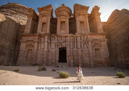 Asian Woman Tourist In White Dress Standing At Ad Deir Or El Deir, The Monument Carved Out Of Rock I