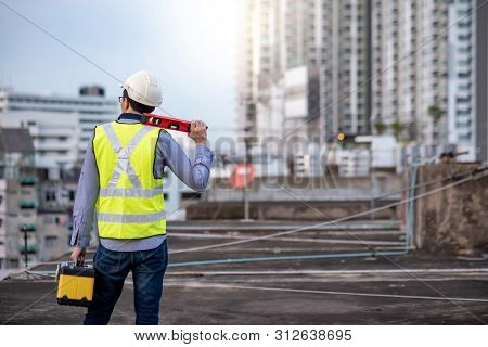 Asian Maintenance Worker Man Holding Red Aluminium Spirit Level Tool Or Bubble Levels And Wprking To