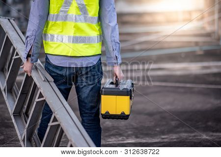 Maintenance Worker Man With Safety Helmet And Green Vest Carrying Aluminium Step Ladder And Tool Box