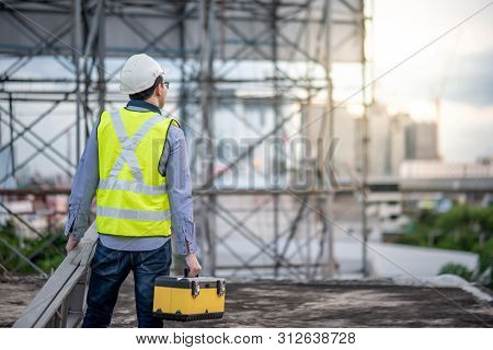 Asian Maintenance Worker Man With Safety Helmet And Green Vest Carrying Aluminium Step Ladder And To