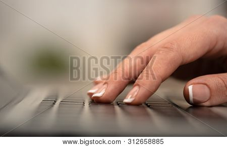 Hand typing on keyboard with office concept