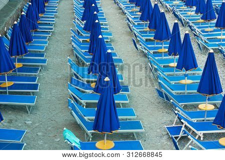 Seaside resort beach with chaise longues and umbrellas