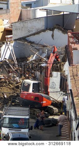 Excavator Demolishing Old Residential Building In Andalusian Village
